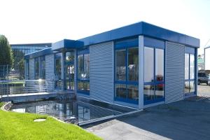 Büropavillonanlage in modulbauweise mit bodentiefen Fenstern und Wellblechfassade